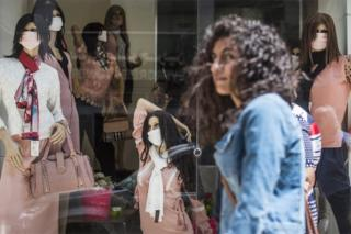 A woman passes in front of mannequins in a shop wearing face masks in street in Cairo, Egypt, on 25 April.