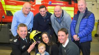 Jade Broderick and baby Blake with firefighters who saved her life on her first birthday, from left, back row, John Mather, Andy Hinde, Dave Morris and Damon Leonard; front row, Gus O'Rourke and Martin Dowle