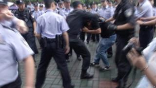 Police scuffle with a protestor outside the municipal government headquarters in Shanghai (27 June 2015)