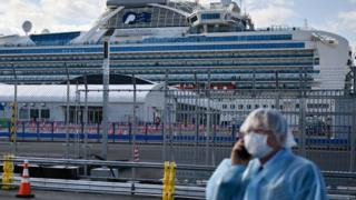 positive people A man in protective gear speaks on the phone near the Diamond Princess cruise ship in quarantine due to fears of the new COVID-19 coronavirus, at the Daikoku Pier Cruise Terminal in Yokohama on February 19, 2020