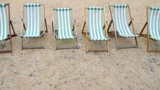 Deckchairs are seen on parched grass in Hyde Park in London.
