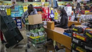 A man pushes a shopping cart full of alcoholic beverages at a supermarket amid the ongoing coronavirus emergency lockdown in Johannesburg, South Africa, 18 August 2020