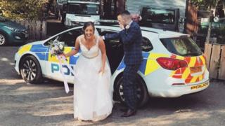 The newly weds getting out of a police car