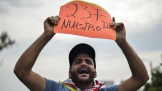 "A man holds a placard reading ""23F Our Day"""