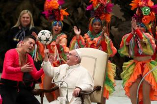 Pope Francis plays with a ball as members of Circus of Cuba perform during the Wednesday general audience in Paul VI Hall at the Vatican, 2 January 2019.