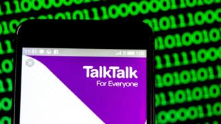 The talktalk logo is seen on a phone here against a background of green binary code in a photo illustration