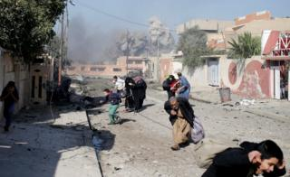 People run in panic after a coalition airstrike hit Islamic State fighters positions in Tahrir neighbourhood of Mosul, Iraq