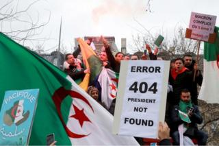 "Protesters hold up flags and placards, one of which reads ""Error 404 president not found"" on 7 March 2019."