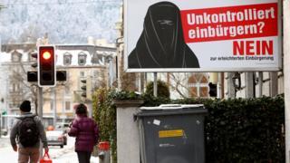 """Orang berjalan dekat poster """"Komite melawan jalan mudah mendapat kewarganegaraan"""" yang ada di dekat stasiun kereta Hauptbahnhof, Zurich, 11 Januari 2017"""