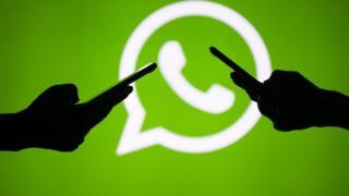 Sombra de dos personas manejando celulares con el logo de WhatsApp de fondo.