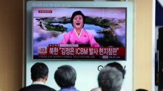 People watch a North Korean state television show as a presenter announces North Korea has test-launched its first intercontinental ballistic missile at the Seoul Railway Station on 4 July 2017 in Seoul, South Korea