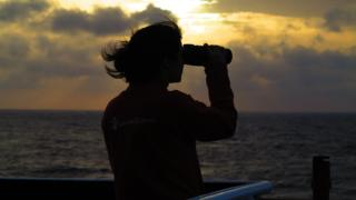 Volunteer looks out to sea through binoculars