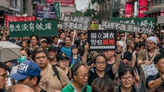 Protesters hold placards and shout slogans as they take part in a rally on a street on July 7, 2019 in Hong Kong