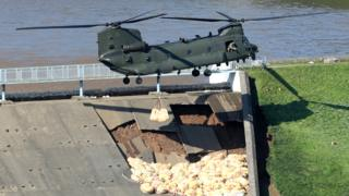 An RAF Chinook helicopter flies in sandbags to help repair a dam at Toddbrook reservoir