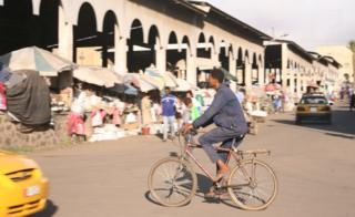 A man cycling past a market in Asmara, Eritrea