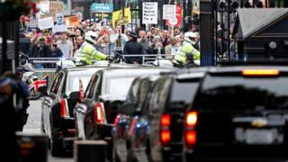 Demonstrators at Downing Street watch motorcade leave
