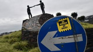 A No Border No Brexit sticker close to the Hands Across the Divide peace statue