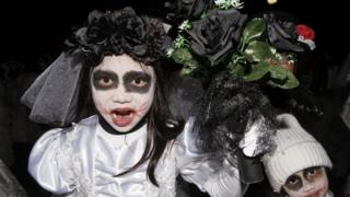 Children wearing zombie-bride costumes
