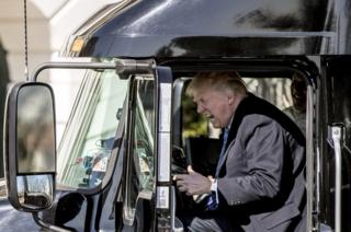President Donald Trump pretends to drive as he gets in an 18-wheeler as he meets with truckers and CEOs regarding healthcare on the South Lawn of the White House, 23 March 2017.