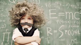 """Imagem mostra menino fantasiado como """"gênio"""", com quadro negro ao fundo"""