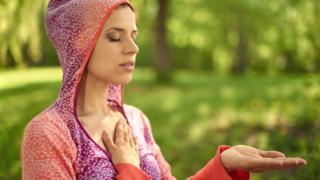 Joven meditando con una mano en su corazón y otra mano abierta y extendida