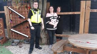 Police officer and volunteers with damaged fence
