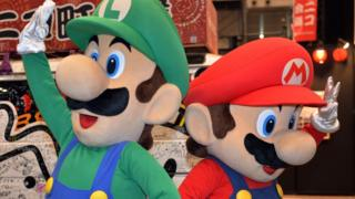 People wave, dressed in costumes as Nintendo characters Mario and Luigi