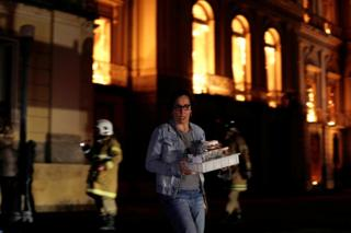 A worker rescues items during a fire at the National Museum