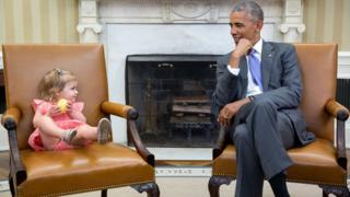 Two matching chairs hold a very young girl in pink, left, and Obama, right, as they share a glance in the White House.