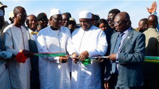 """Les présidents Macky Sall et Adama Barrow coupant le ruban inaugural du """"pont de la Sénégambie""""."""