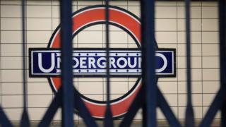 A London Underground sign seen through locked gates.