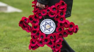 A man lays a wreath during a Holocaust Memorial Day commemoration event at the Imperial War Museum in London