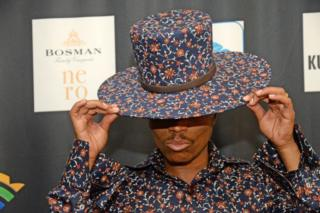 A man tips his printed hat, which matches the print on his shirt, on the red carpet at the South African Film and Television Awards (SAFTAs) at the Sun City Superbowl on 2 March 2019, in Rustenburg.