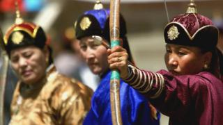 Women dressed in traditional Mongolian clothing compete against each other in archery matches