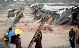 People gather around their shops after they were swept away by flash floods triggered by heavy rains