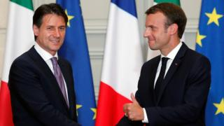 French President Emmanuel Macron (R) and Italian Prime Minister Giuseppe Conte shake hands after a joint press conference following their meeting at the Elysee presidential Palace in Paris