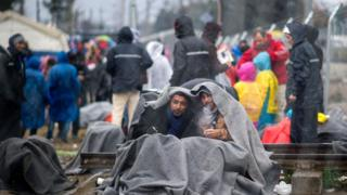 Migrants from Syria wait to cross the Greek-Macedonian border near the town of Gevgelija on February 24, 2016