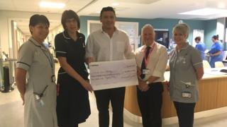 Terry Garnett holding a giant cheque alongside hospital staff