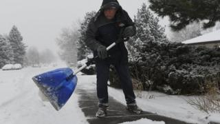Мужчина убирает снег в Денвере