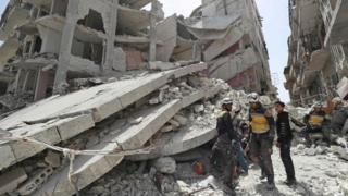 Rescue workers from the Syria Civil Defence, also known as the White Helmets, search the rubble of a collapsed building following an explosion in the opposition-held town of Jisr al-Shughour (24 April 2019)