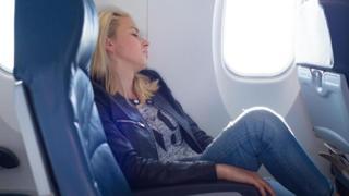 Mulher dormindo no avião