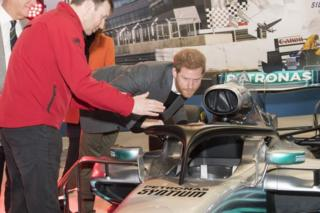 "Prince Harry, studies the ""Halo"" on Lewis Hamilton""s Mercedes, a new safety addition to Formula 1 cars this year, during a visit to the Silverstone Circuit in Northamptonshire"
