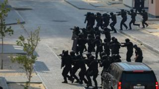 Security forces dressed in black cross a road in preparation for a practice raid