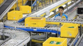 Man next to conveyor belt in Alibaba fulfilment centre.