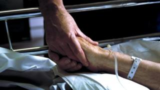 Holding the hand of an elderly patient in a hospital bed