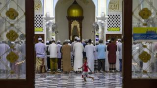 Thai men attend the evening prayer as a boy runs across the floor at the Pattani Central mosque, in Pattani, Thailand.