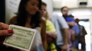 Mulher segura título de eleitor em frente a fila de votação em Brasília