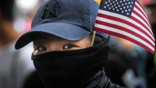 带着美国国旗游行的蒙面示威者