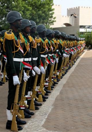 in_pictures Uniformed military guards holding gold-coloured rifles stand at ease.