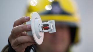 Technical Fire Safety Officer holding up a sprinkler